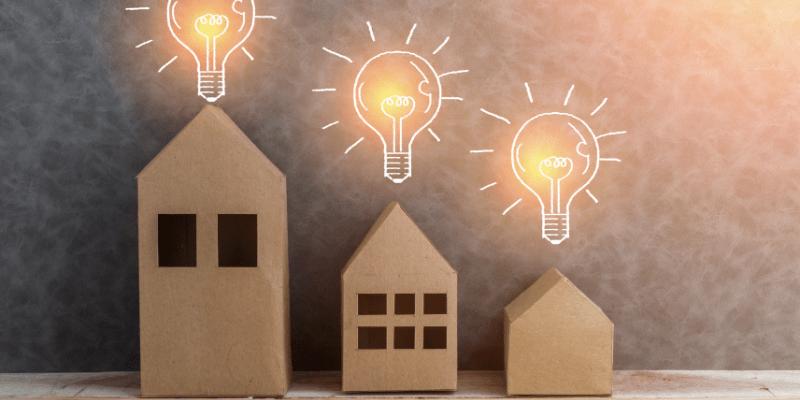 Trois ampoules idées surmontant trois maisons en cartons, représentant les idées pour choisir un fournisseur d'éléctricité pour un bien neuf