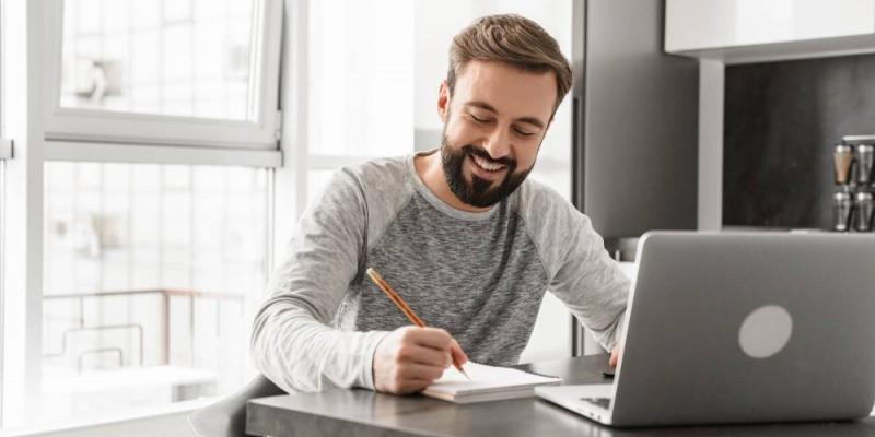 Jeune homme devant son ordinateur portable calculant sa capacité d'emprunt