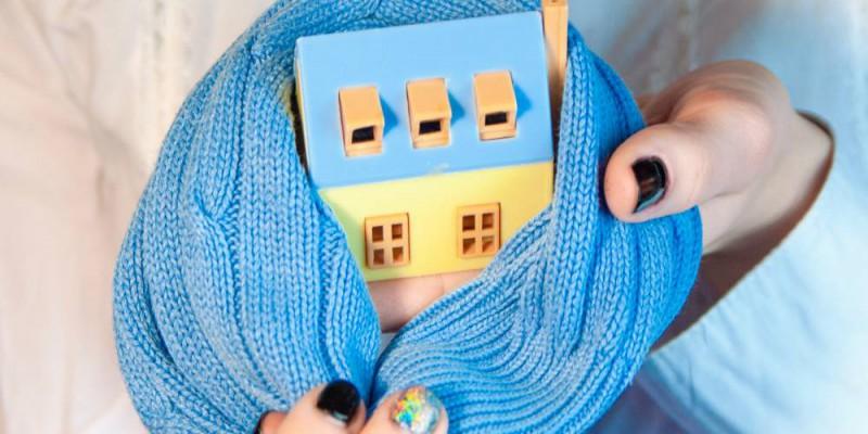 Maison en bois miniature avec une petite écharpe bleue entre les mains d'une femme