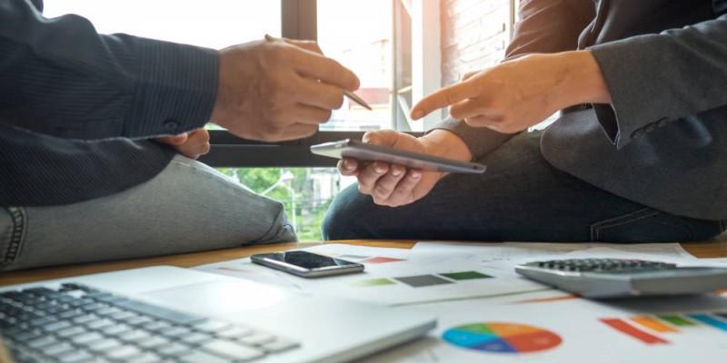 deux hommes préparant le bilan prévisionnel de l'entreprise pour lever des fonds