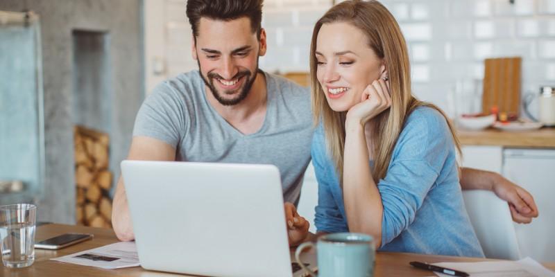 Un couple effectue un rachat de prêts personnels devant leur ordinateur