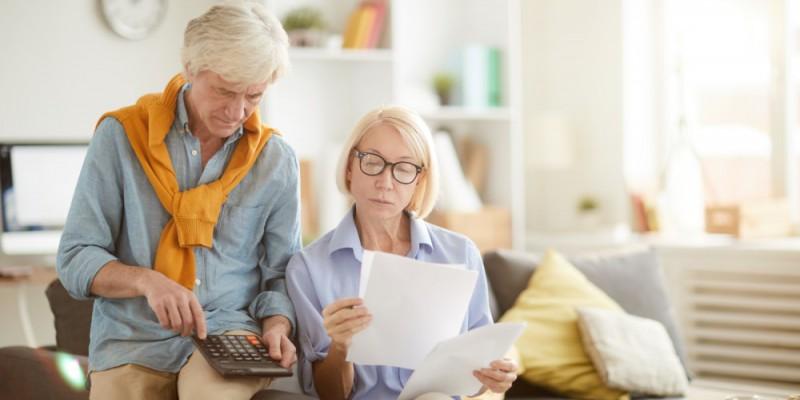 Couple senior vérifiant le calcul de la taxe d'habitation