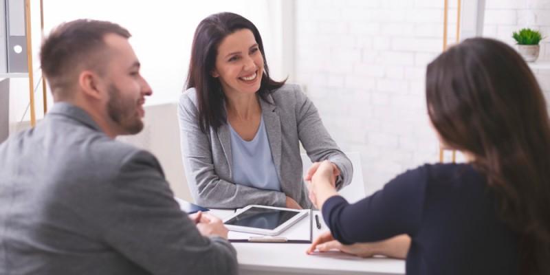 Courtière souriante et confiante serrant la mains des emprunteurs