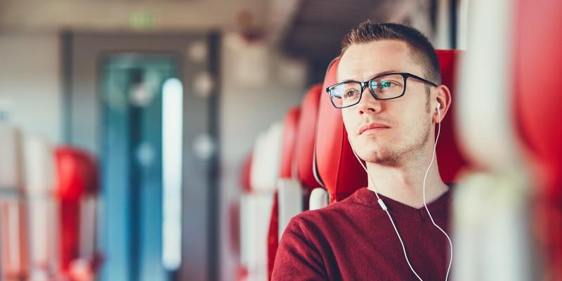 Un étudiant est assit dans le train et attend une réponse pour savoir si son prêt étudiant peut faire office à un rachat de crédits