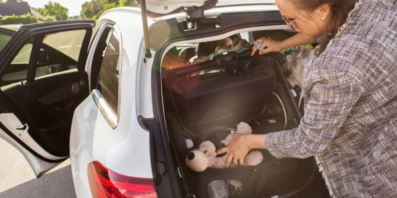 Femme chargeant la nouvelle voiture avec sac et doudous des enfants