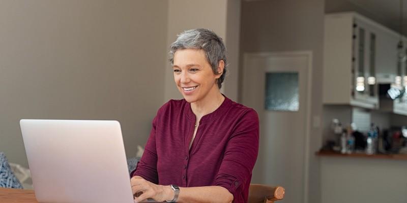 Une femme est devant son ordinateur et fait une demande pour racheter son rachat de crédits
