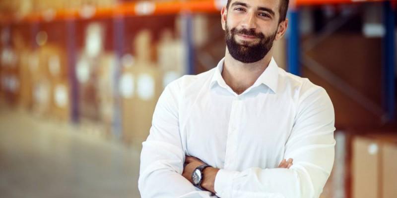 Entrepreneur bras croisés confiant devant son stock de marchandise