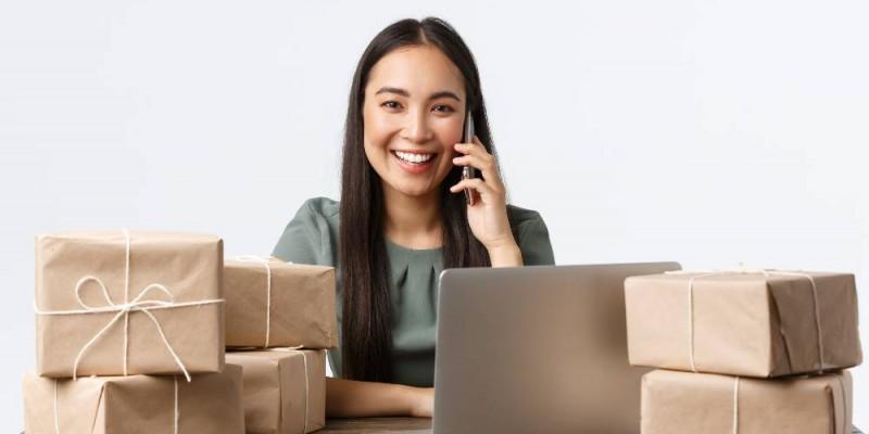 Femme entrepreneure souriante devant son ordinateur au milieu colis pour ses clients
