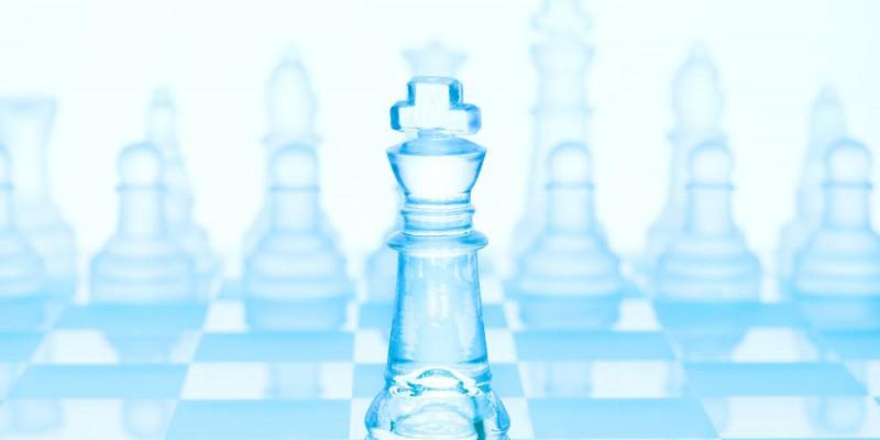Jeu d'échec en verre de teinte bleuté. Le roi est placé en avant plan.