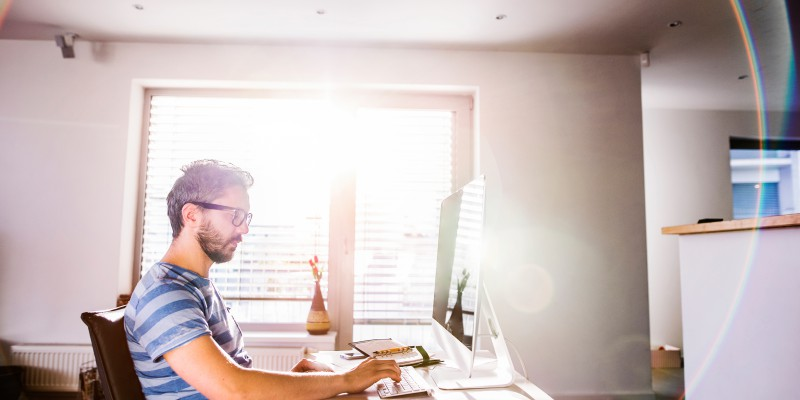 homme assit seul à son bureau devant son ordinateur fait une demande de rachat de crédits