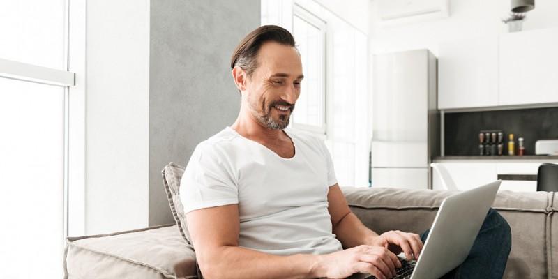 homme assit devant ordinateur content grâce à un rachat de crédits