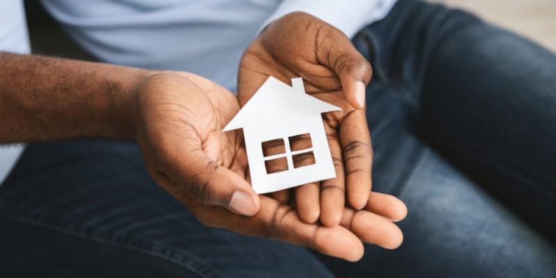 homme tenant une petite maison en carton entre ses mains