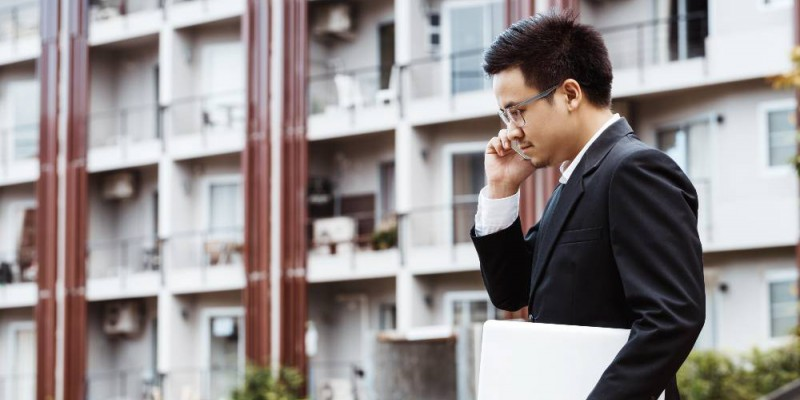 Homme au téléphone devant un immeuble composé d'appartements