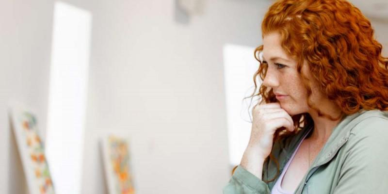 Jeune femme rousse réflechissant dans une galerie d'art