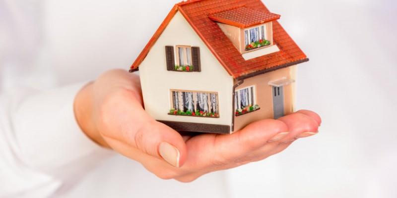 maison miniature posée sur une main