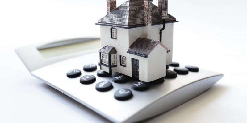 Maison posée sur une calculatrice pour la taxe foncière