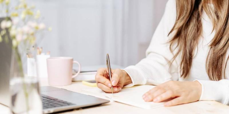 femme prenant des notes devant son ordinateur