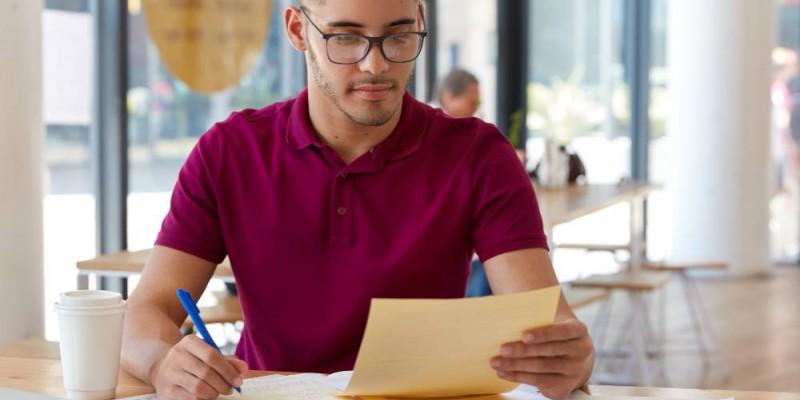 jeune homme à lunettes calculant ses indemnités de remboursement anticipé