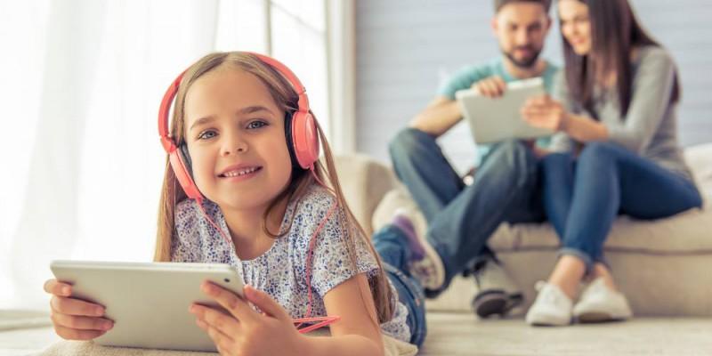 Couple de parents et leur fille souriant regardant leurs tablettes respectives.