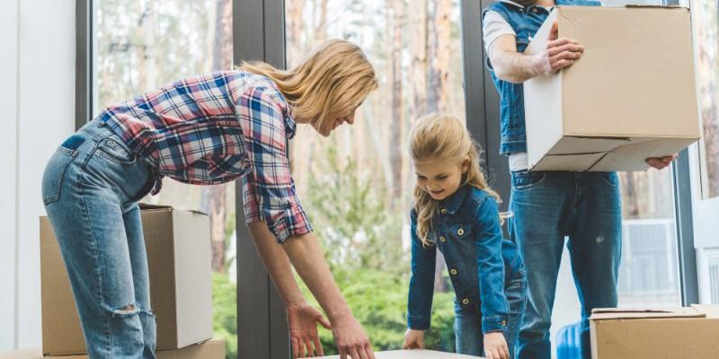 famille, parents et leurs fille, transportant leurs cartons de déménagement