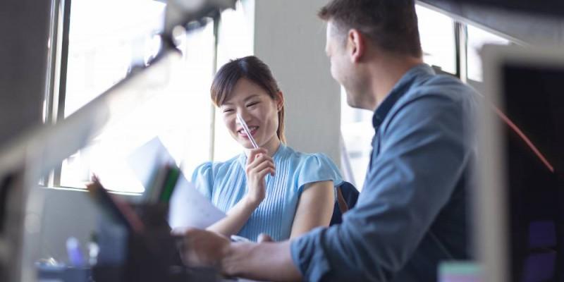 Un homme et une femme, collaborateurs, souriants