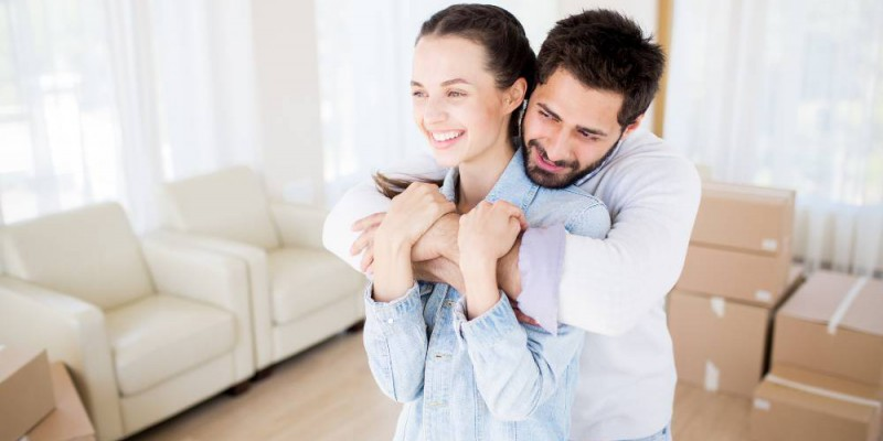 Couple souriant venant d'emménager dans leur nouvelle maison