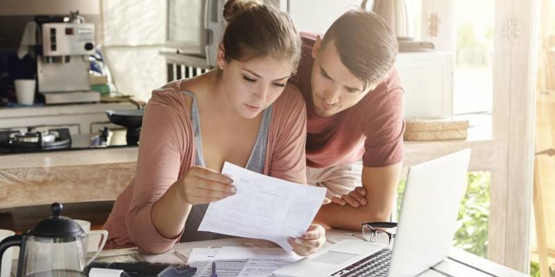 couple faisant le calcul de sa capacité d'emprunt sur un ordinateur portable dans la cuisine