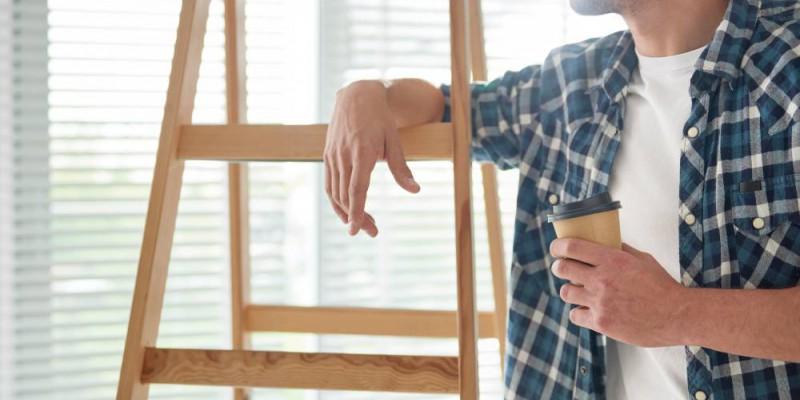 homme accouché à échelle en bois prenant une pause café durant ses travaux